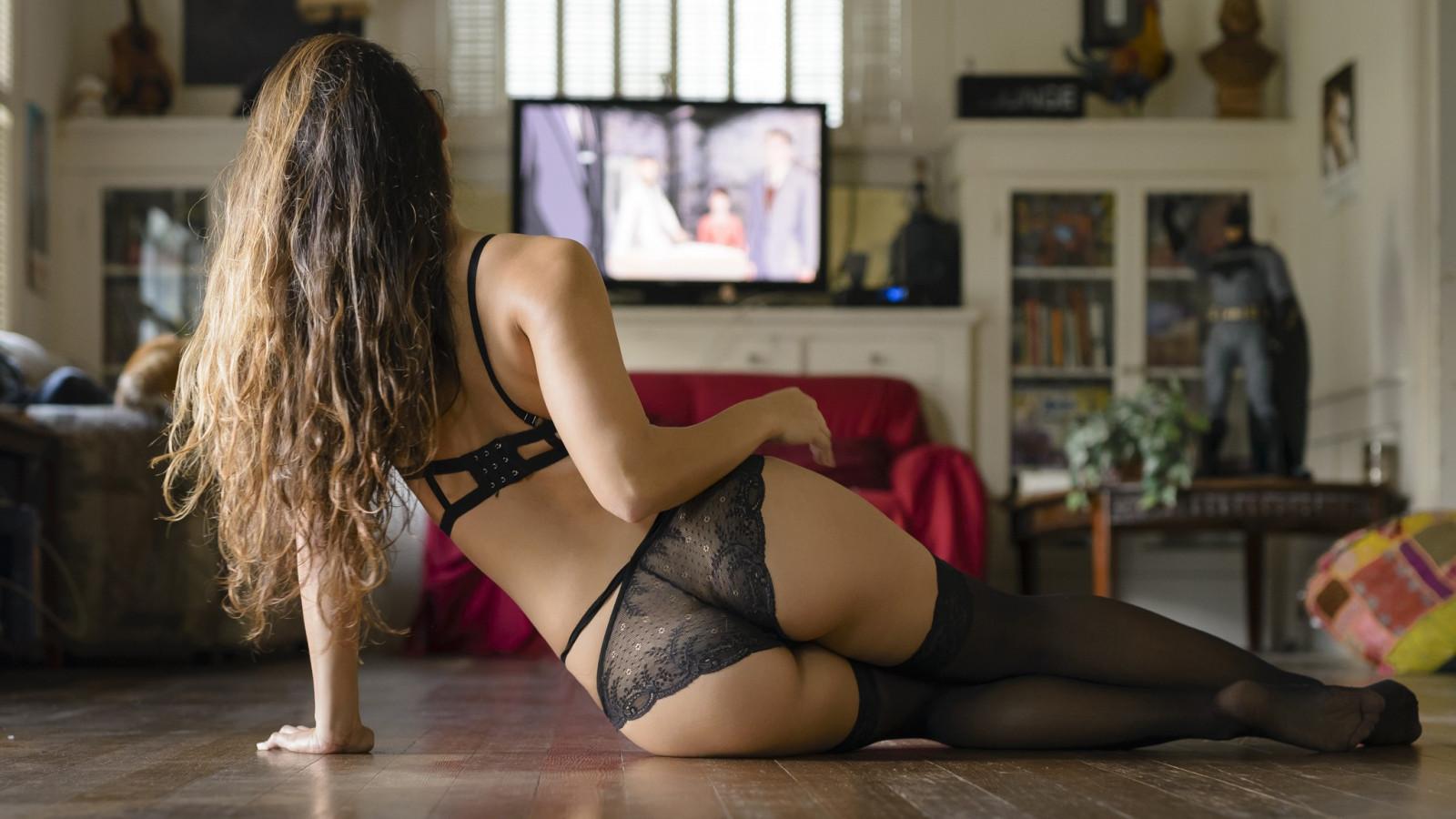 Брюнетка с длинными ногами в черных чулках на полу фото